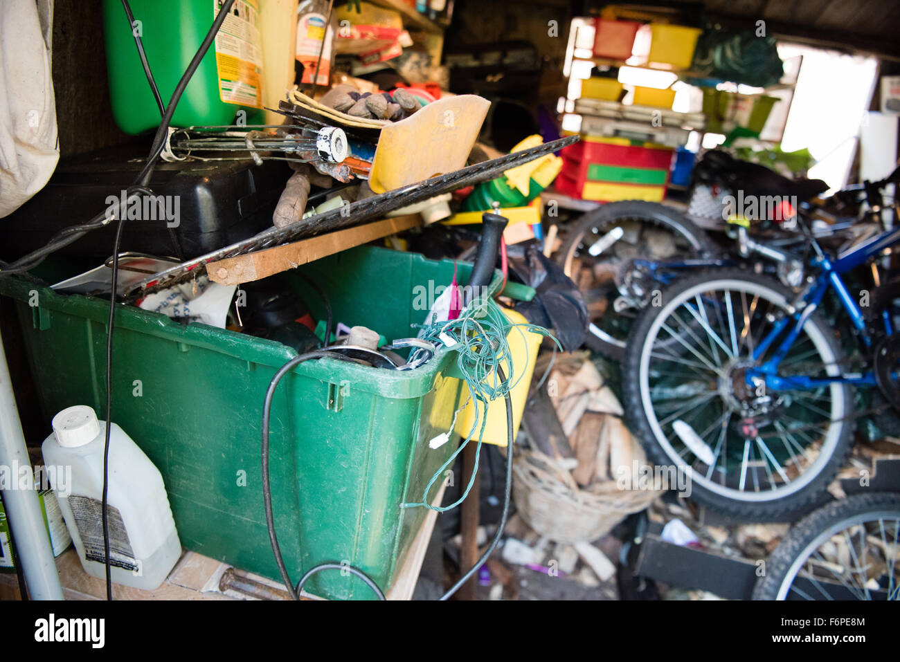 Inside a messy and cluttered wooden garage shed with tools, bikes and garden equipment piled up on uneven shelves - Stock Image