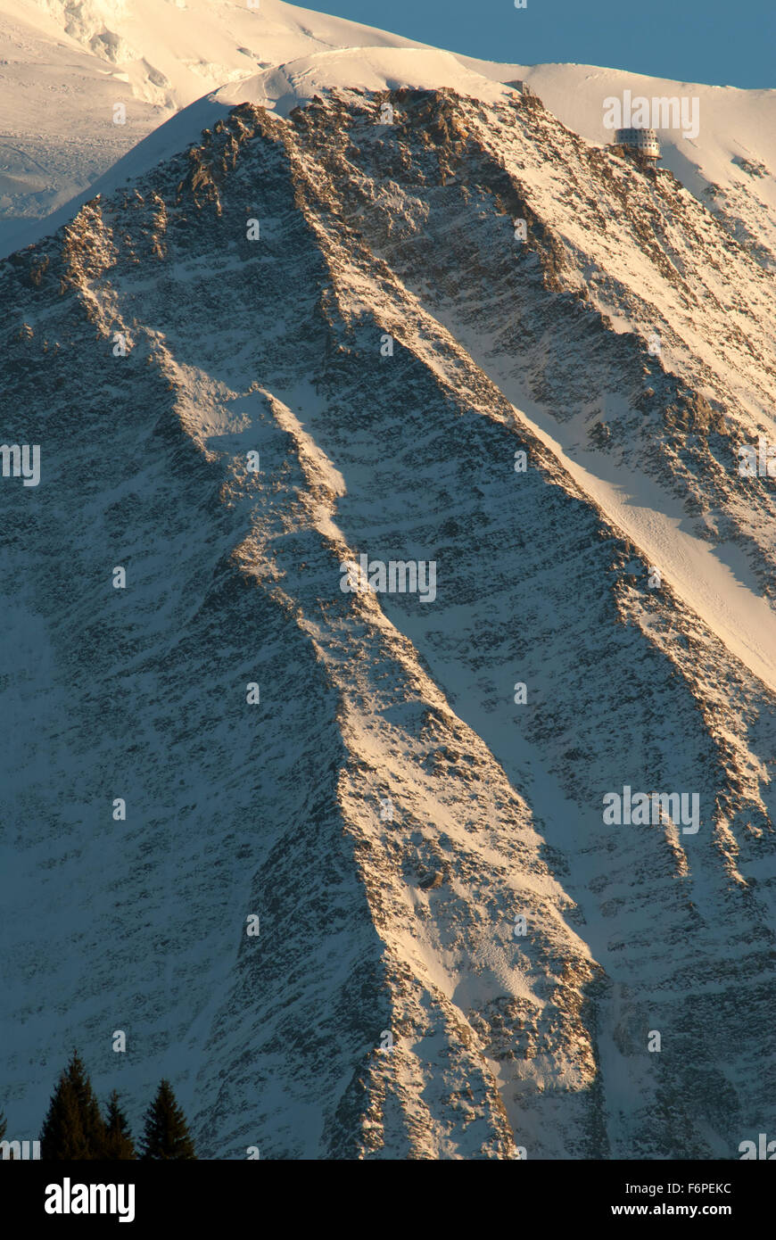 Steep snow dusted slopes of the Aguille de Gouter with the new Gouter mountain refuge glistening in the afternoon - Stock Image