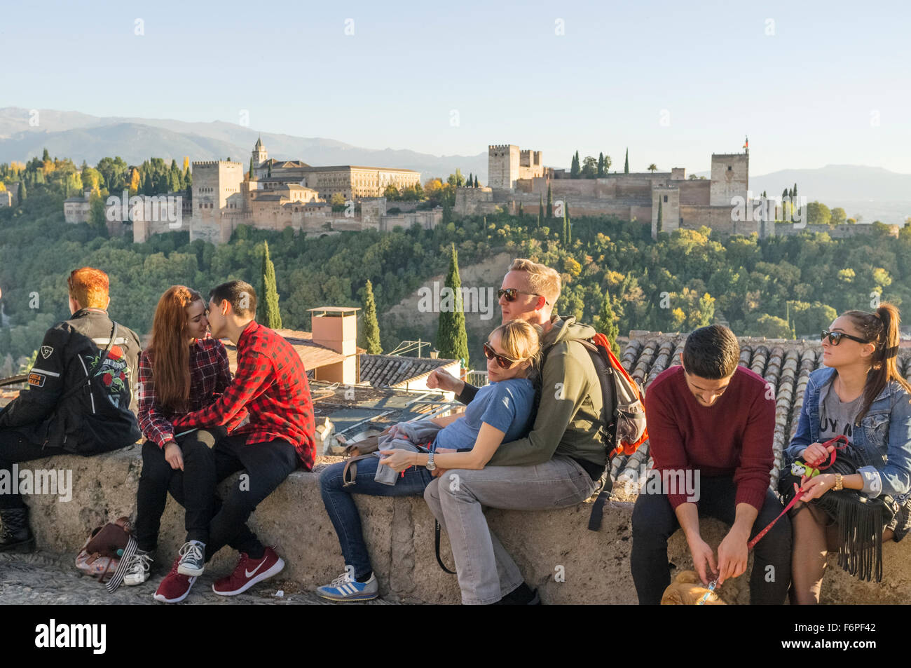 Tourists and couple kissing at the Mirador San Nicolas in the Albaicin with Alhambra in background. Granada, Spain - Stock Image