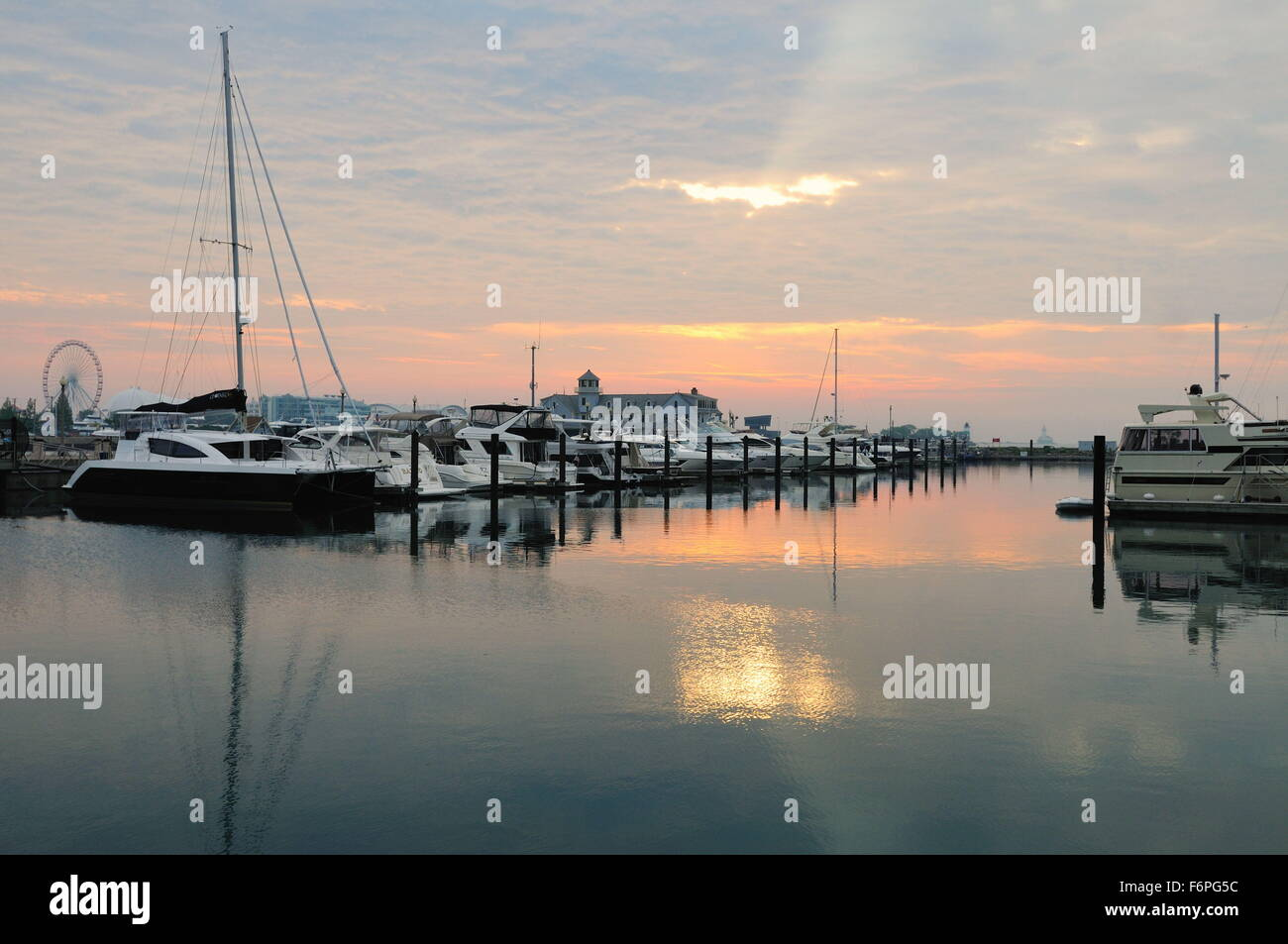 Not long after sunrise the sun attempts to break through cloud cover above pleasure craft in Chicago's DuSable - Stock Image