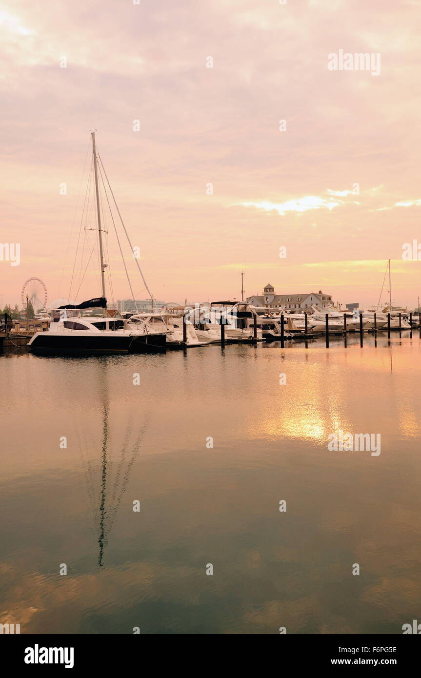 Not long after sunrise the sun attempts to break through cloud cover above pleasure craft in DuSable Harbor. Chicago, - Stock Image