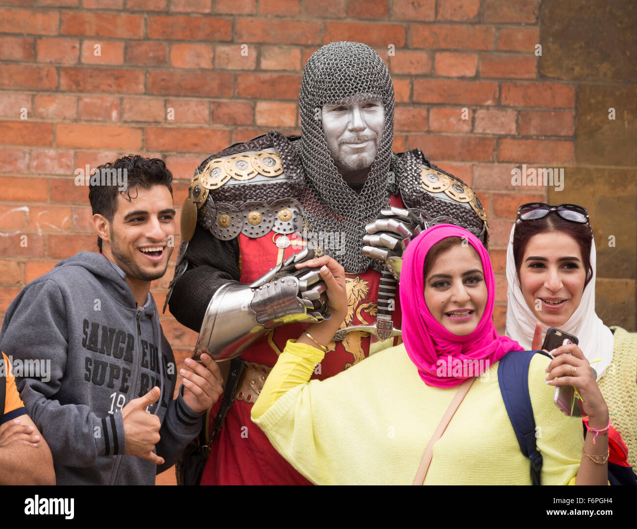 An ethnic family pose with a knight in stratford upon avon the birthplace of shakespeare - Stock Image