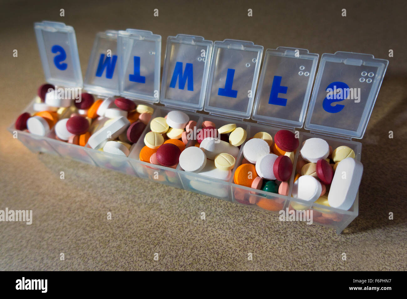 pill medication organizer filled to capacity - Stock Image