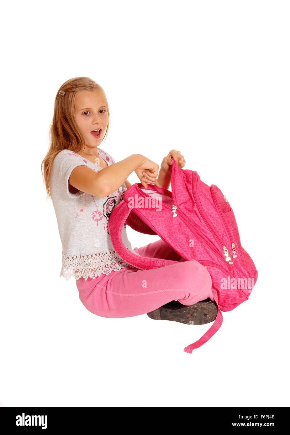 A beautiful young girl opening her pink backpack, pointing into it and is spruced what she find, isolated for white - Stock Image