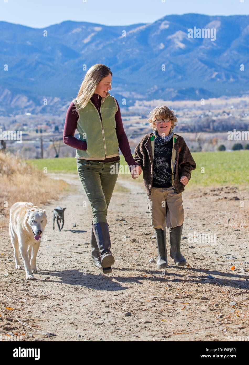 Attractive mother; young son and pet dogs walking along dirt path on ranch - Stock Image