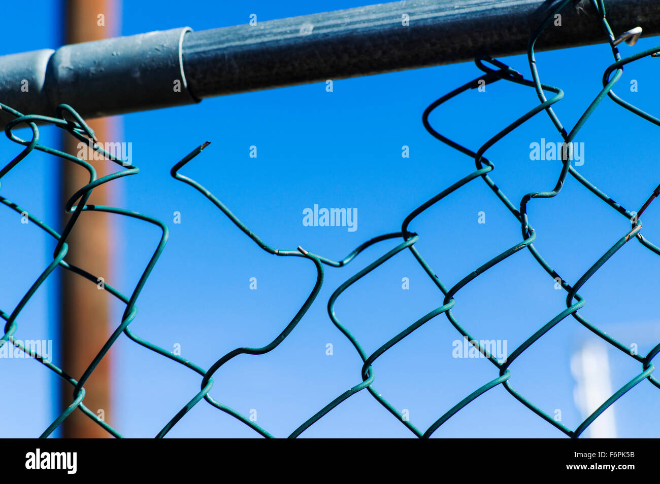 Torn hole in a wire mesh, hurricane, or cyclone steel fence Stock Photo