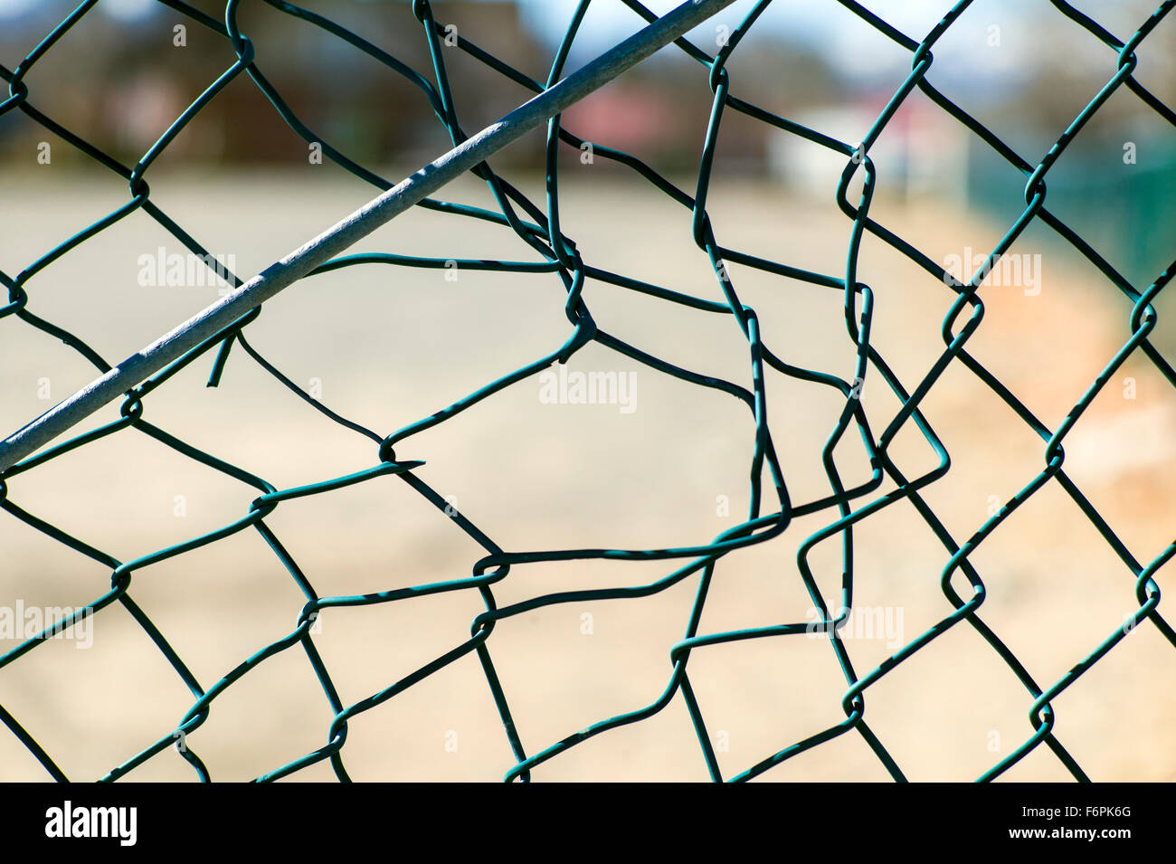 Torn hole in a wire mesh, hurricane, or cyclone steel fence - Stock Image