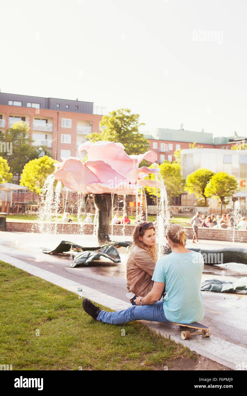 Couple sitting on skateboard at park with fountain in background Stock Photo