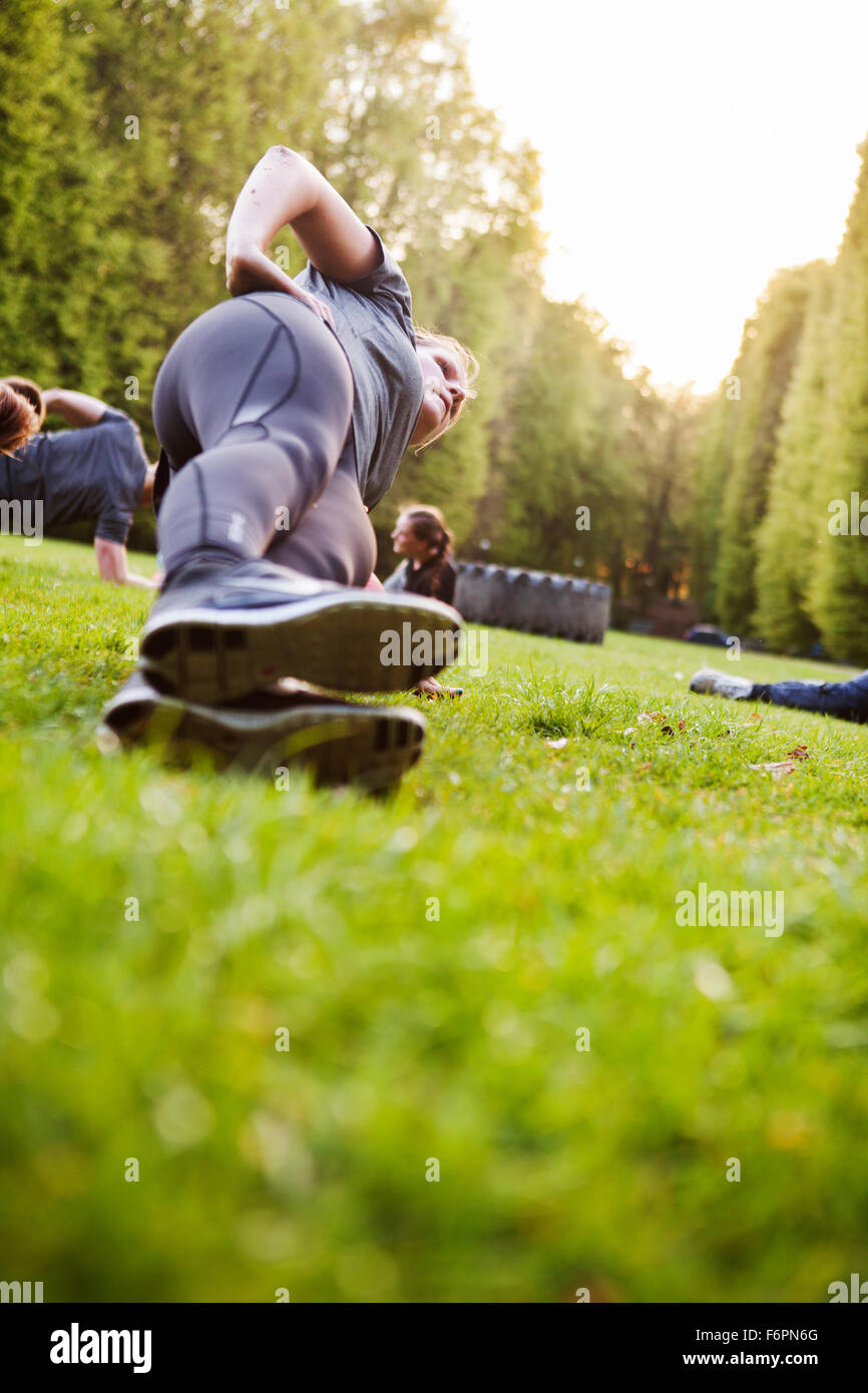 Friends doing side plank on grassy field - Stock Image