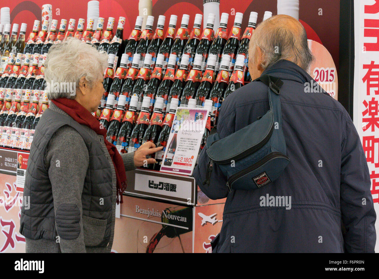 People look at the Beaujolais Nouveau red wine bottles on sale outside the Bic Camera electronics store in Ginza - Stock Image