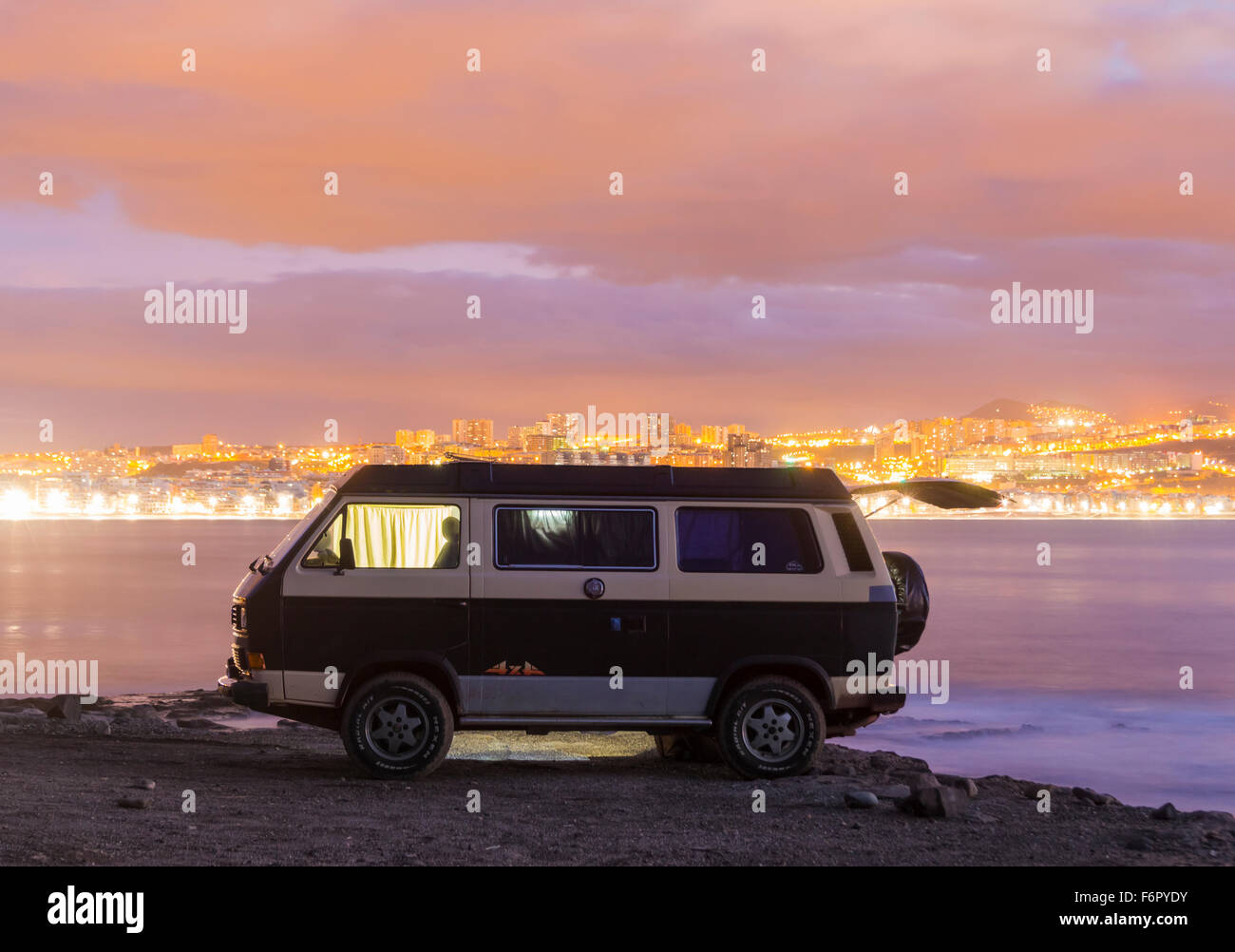 VW camper van parked on beach with city lights in background - Stock Image