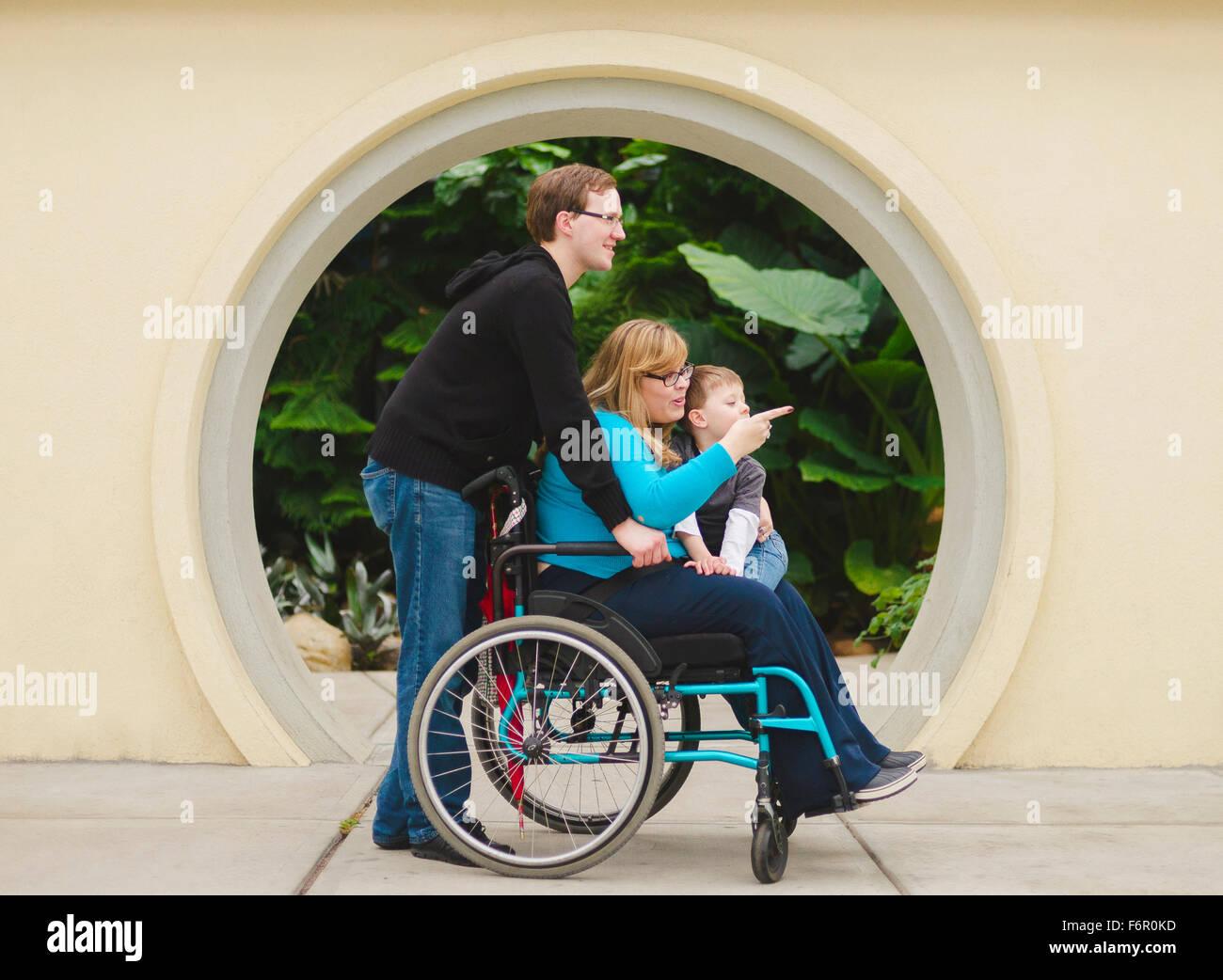 Man pushing paraplegic wife and son Stock Photo
