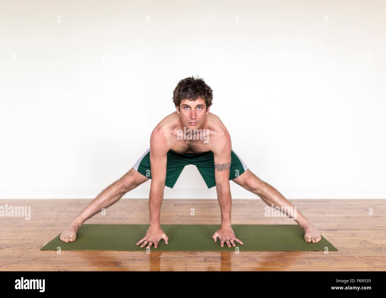 Man practicing yoga in studio - Stock Image