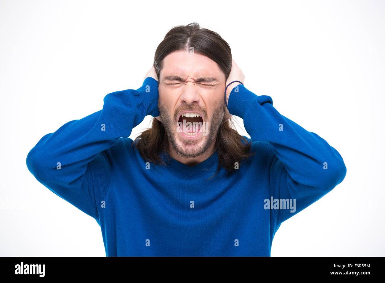 Desperate hysterical angry man with long hair closed ears by hands and screaming with opened mouth - Stock Image