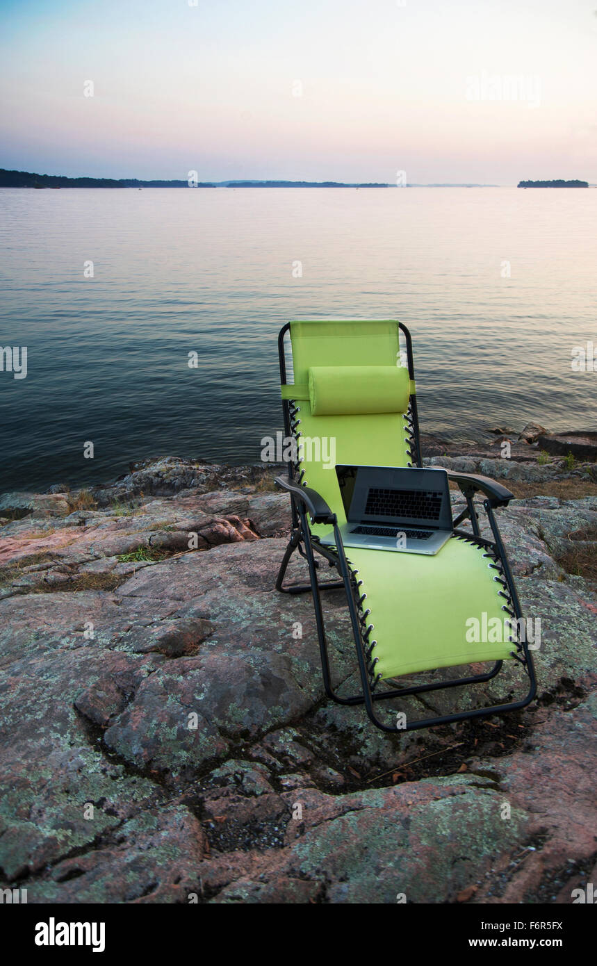 Laptop on lawn chair near remote river - Stock Image