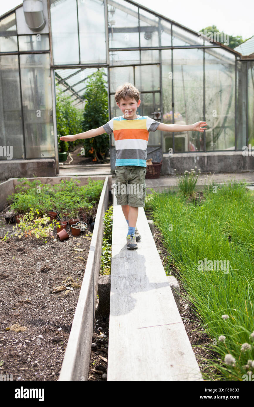 Boy playing in front of greenhouse - Stock Image