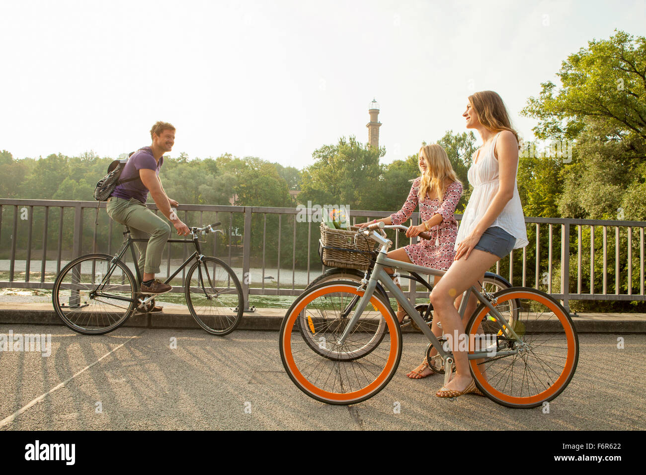 Group of friends riding bicycle on city bridge Stock Photo