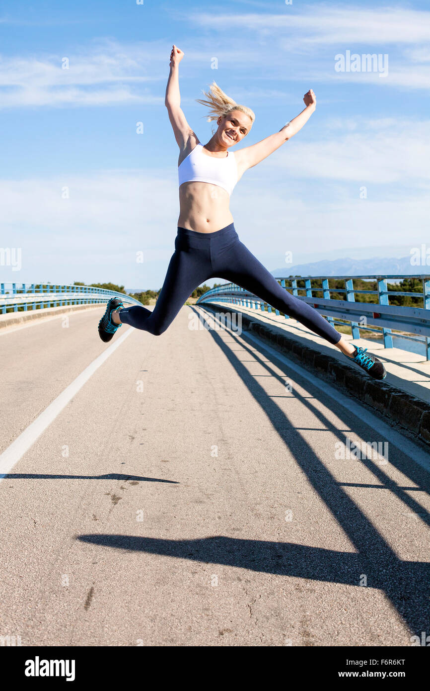 Young woman jumping for joy on the waterfront - Stock Image