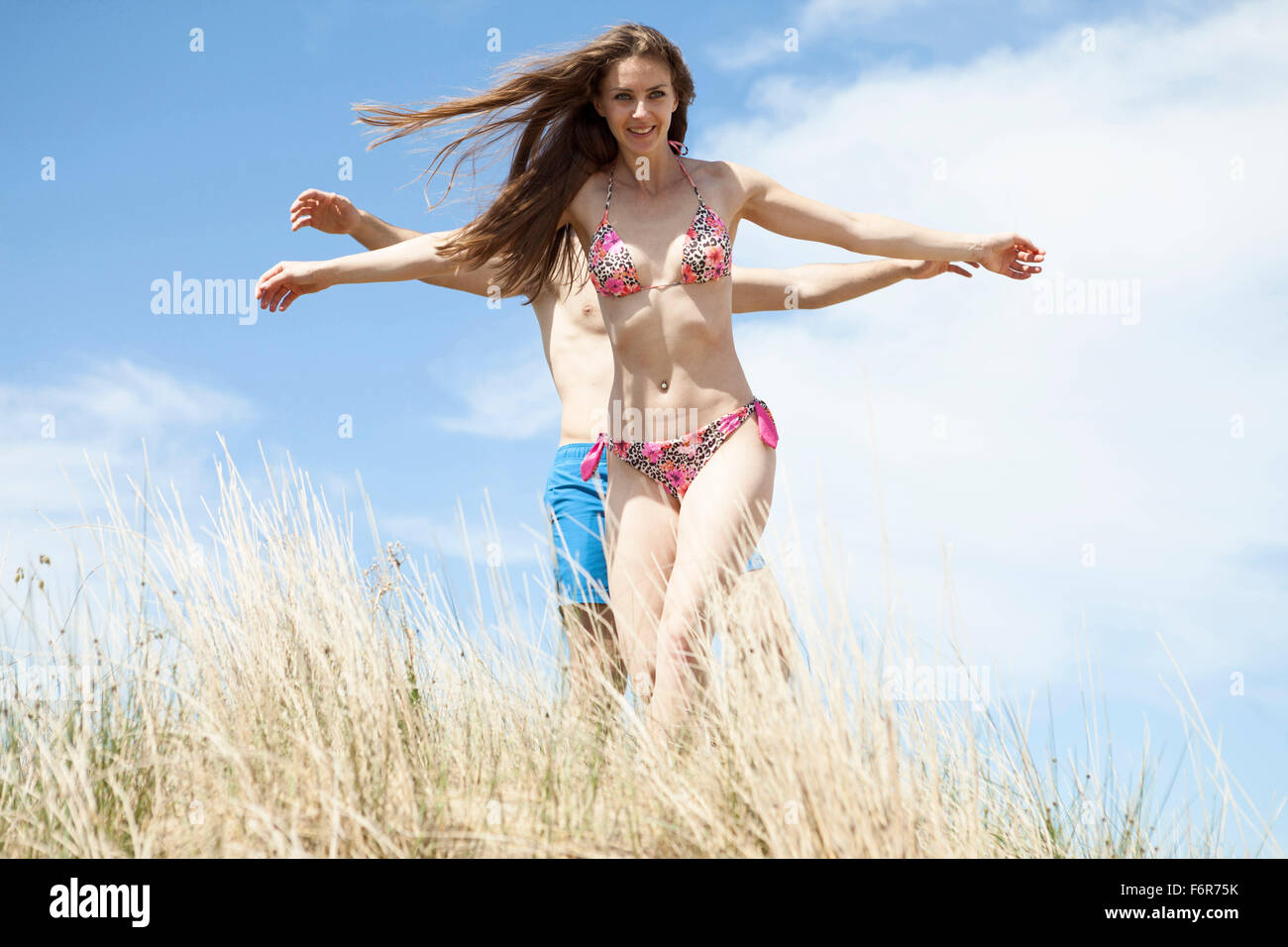 Happy young couple on beach fooling around - Stock Image
