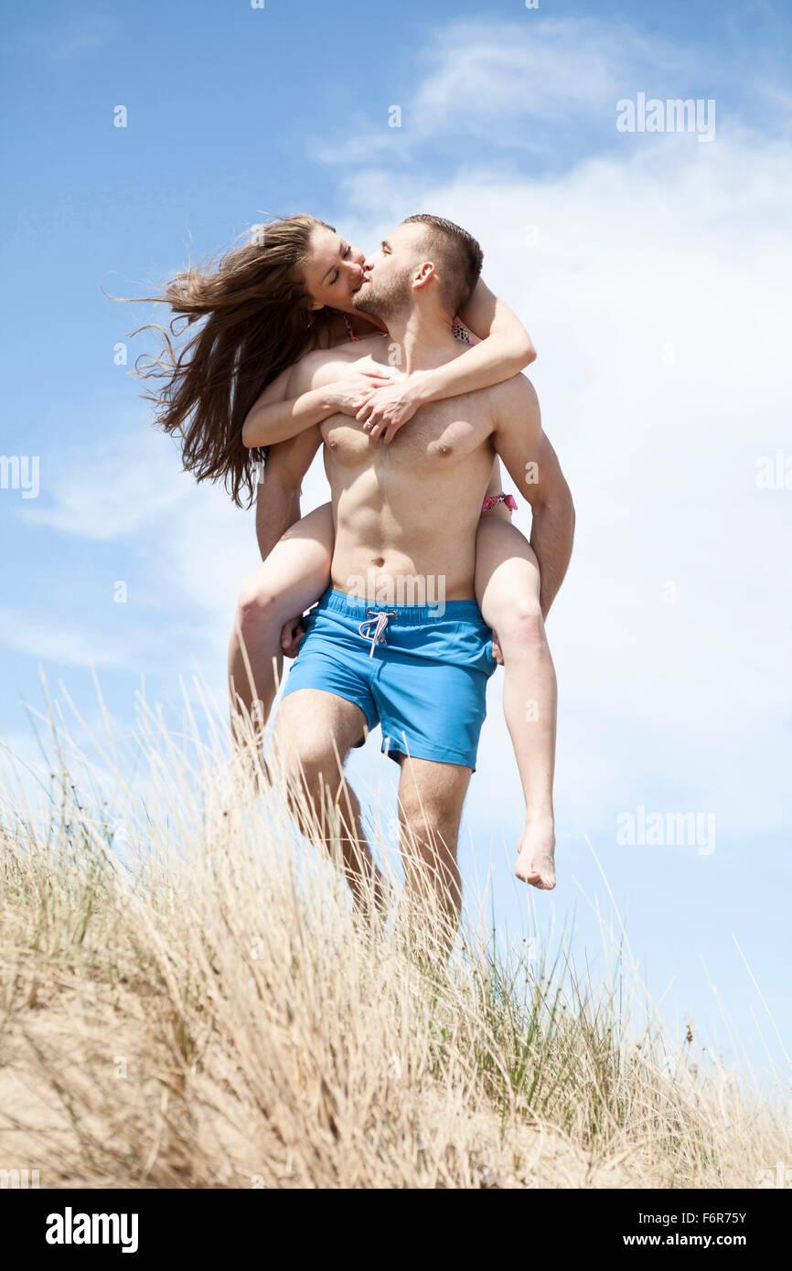 Man giving girlfriend piggyback ride on beach - Stock Image