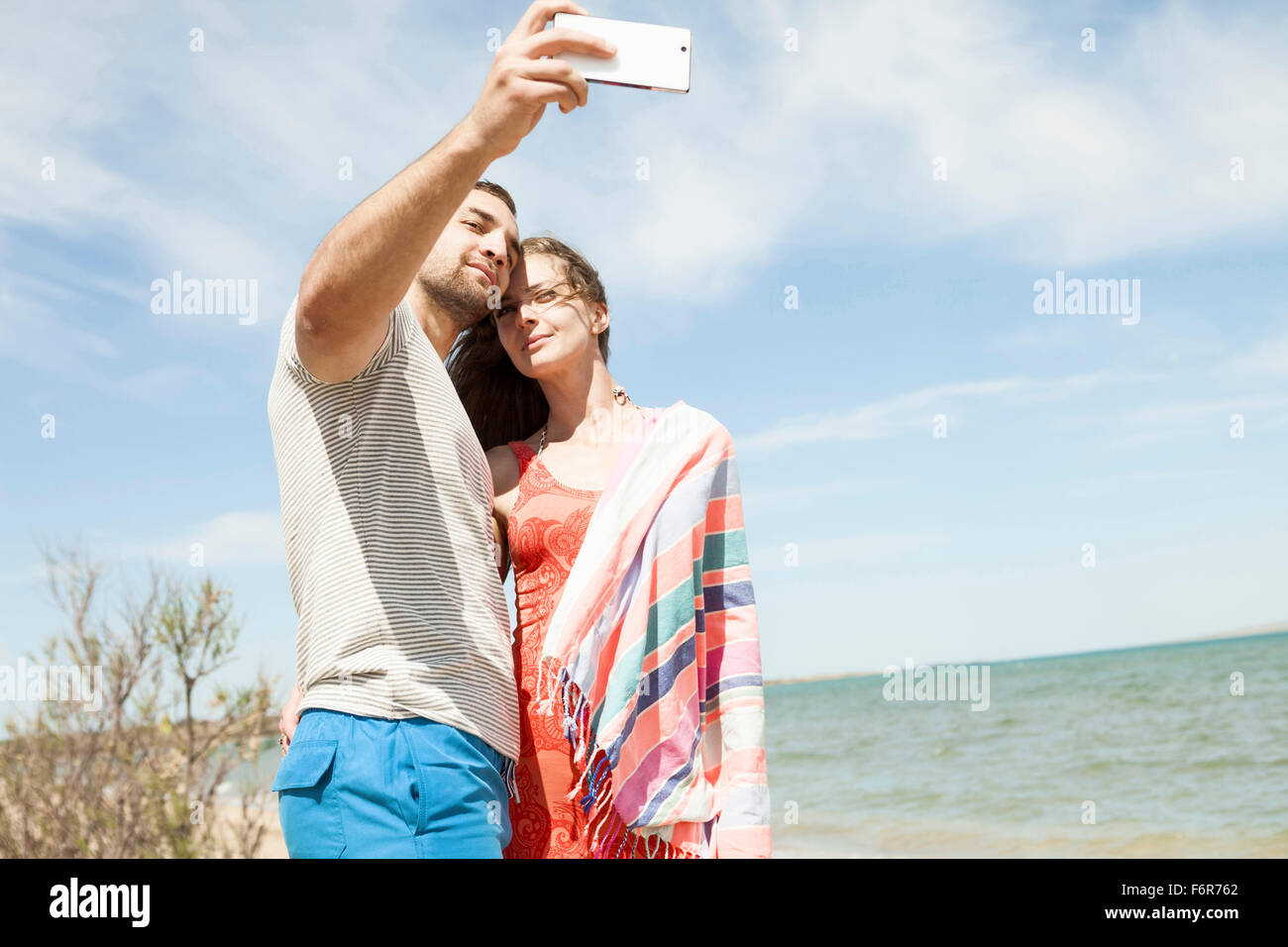 Young couple taking a self portrait on beach - Stock Image