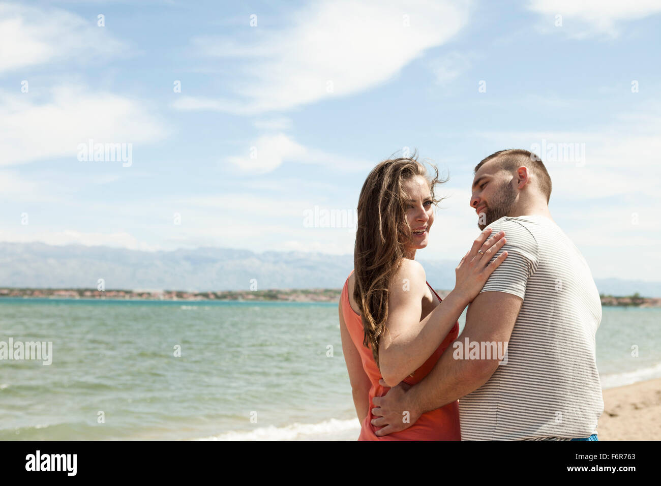 Young couple flirting on beach - Stock Image