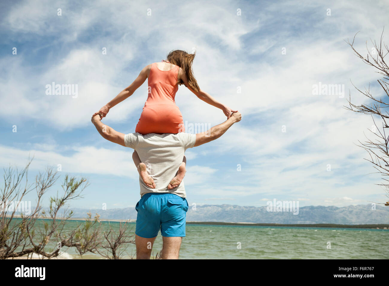 Young woman sitting on shoulder of her boyfriend - Stock Image