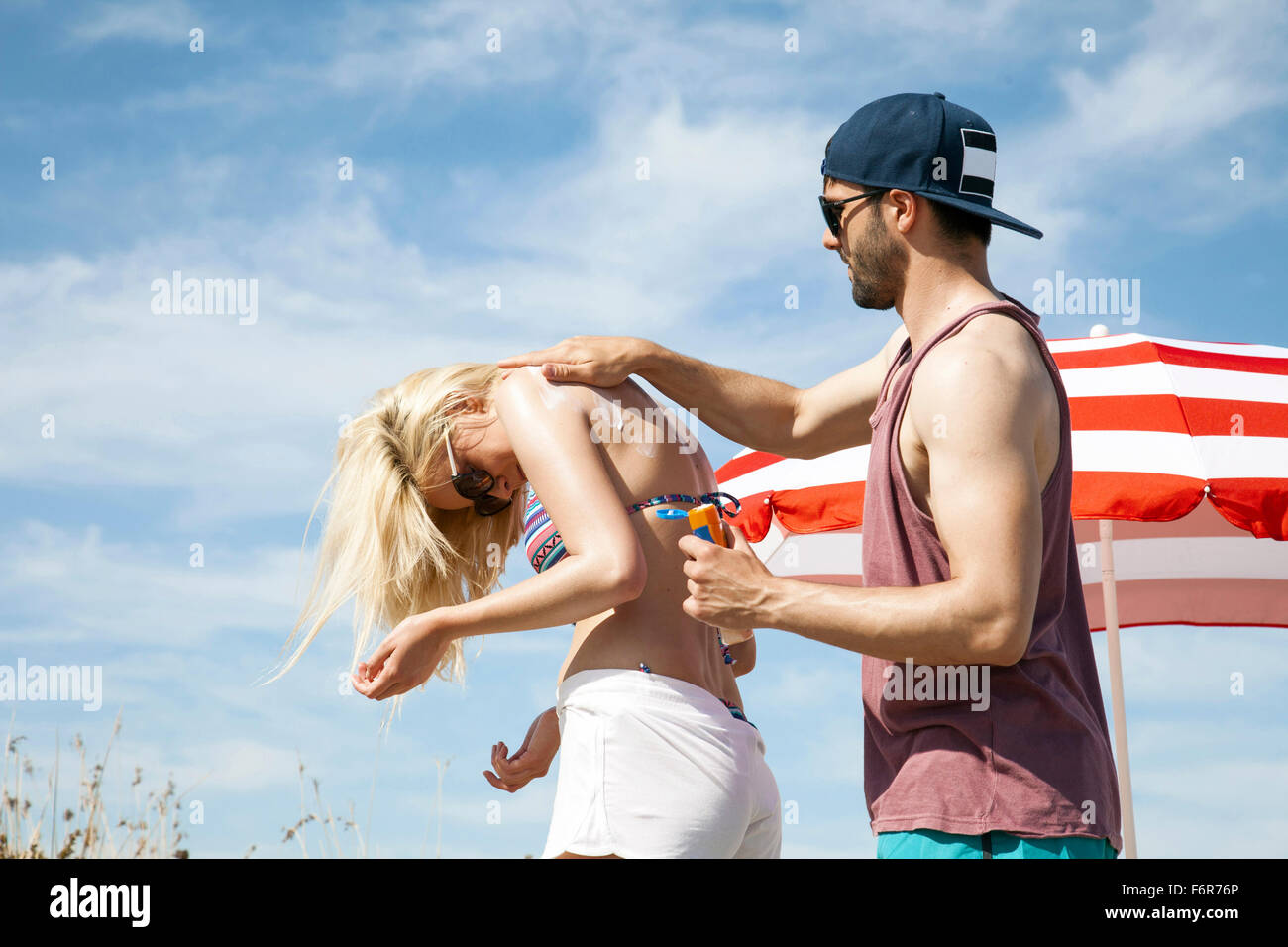 Man applying suntan lotion on woman's back - Stock Image