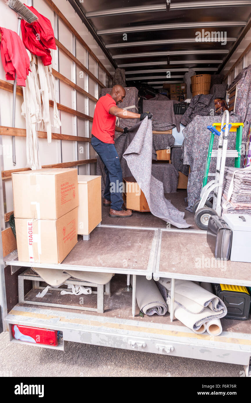Removal men packing a removal van helping family move house in the Uk - Stock Image