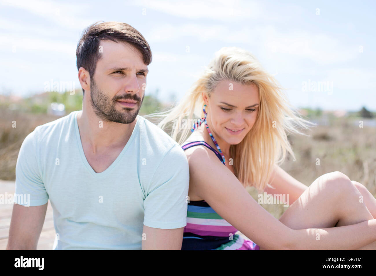 Young couple sitting side by side on beach - Stock Image