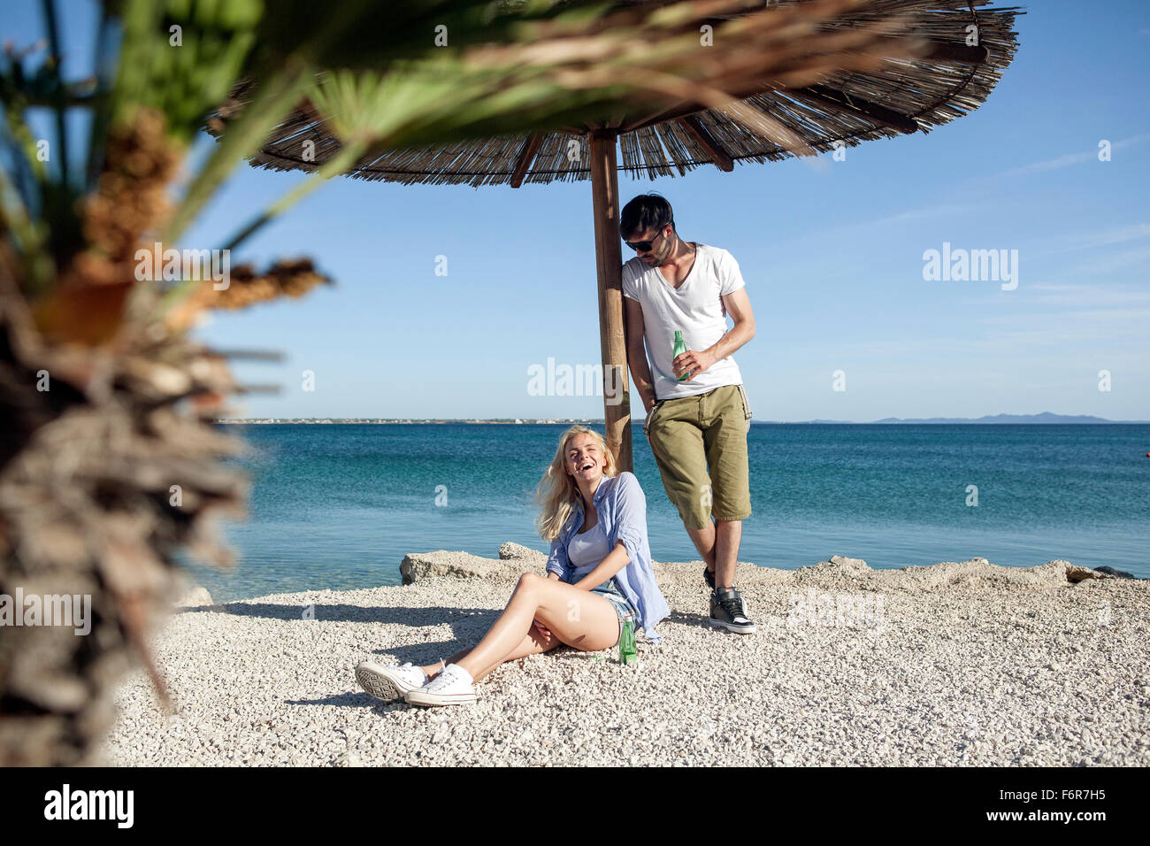 Young man pouring water on girlfriend on beach - Stock Image