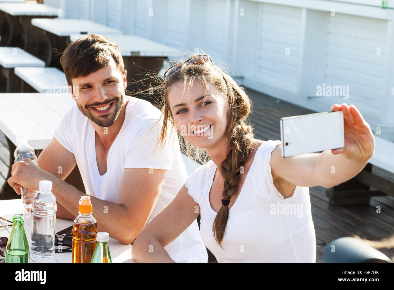 Young couple taking a self portrait in beach bar - Stock Image