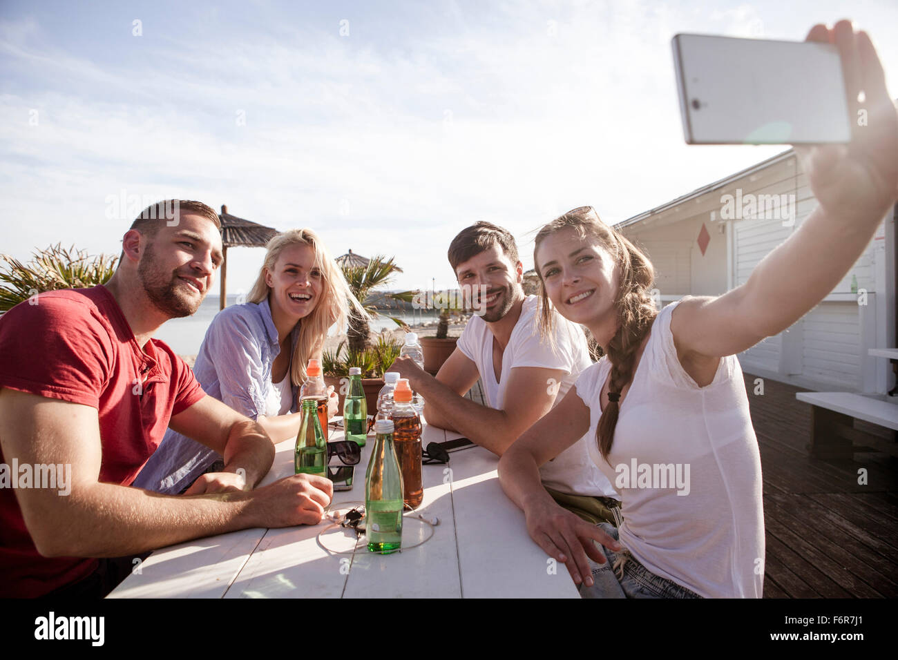 Group of friends taking a self portrait in beach bar - Stock Image