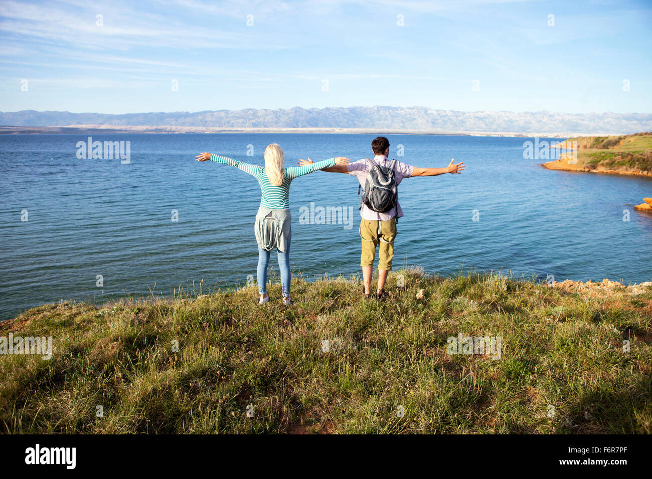 Young couple standing on cliff arms outstretched - Stock Image