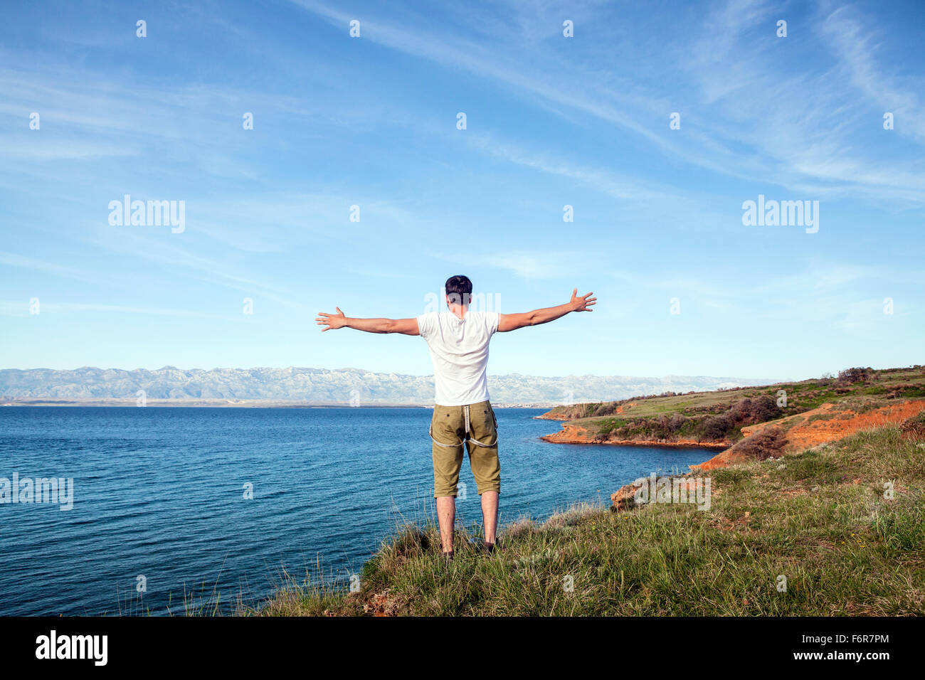 Young man stands on cliff arms outstretched - Stock Image