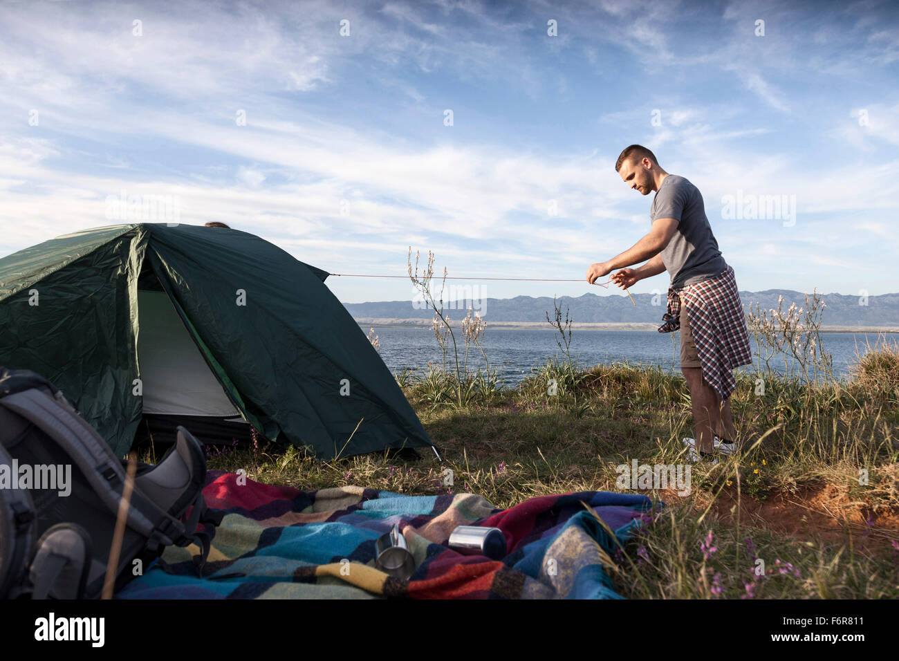 Young man building up tent on water's edge - Stock Image