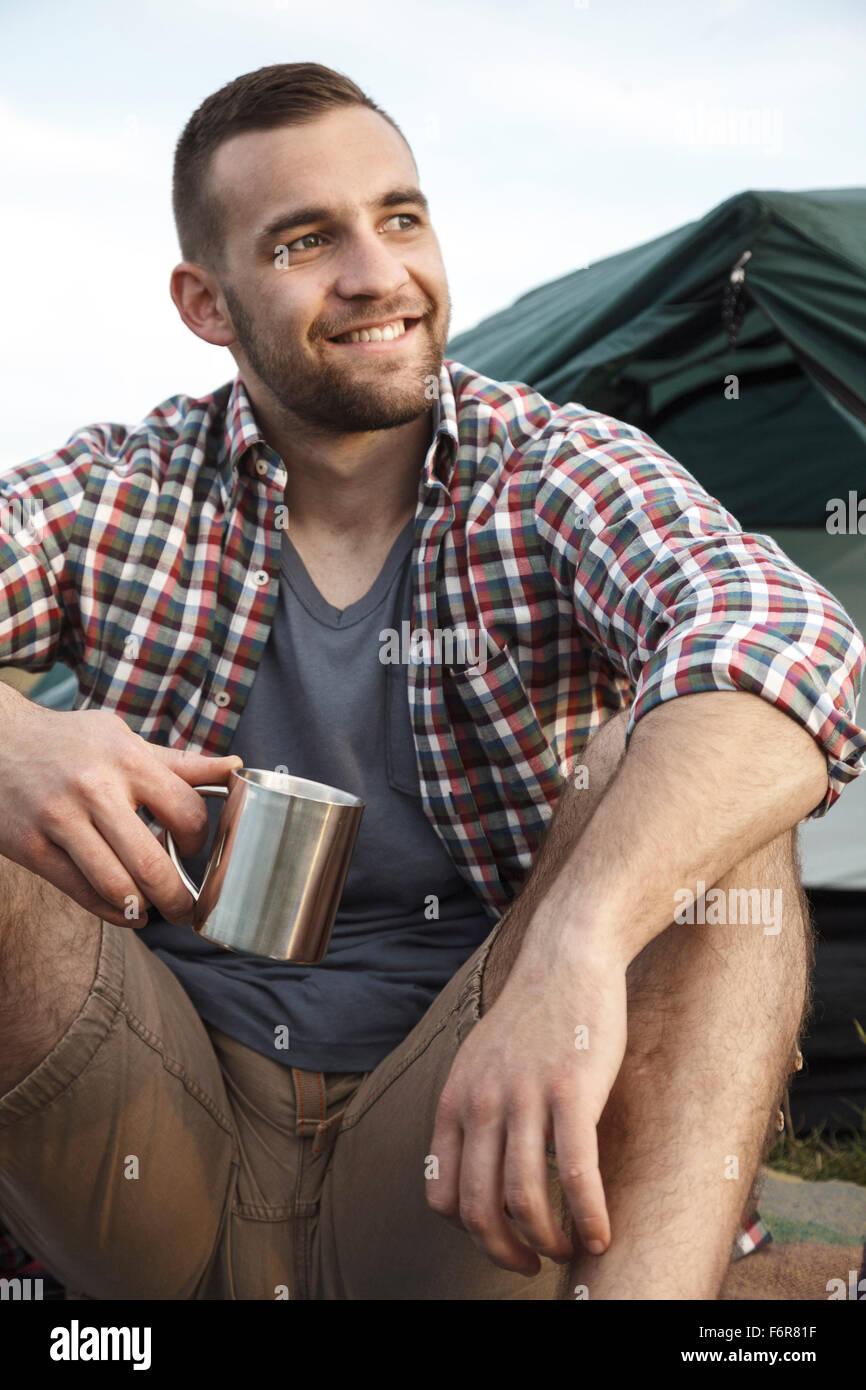 Young man at campsite day dreaming - Stock Image