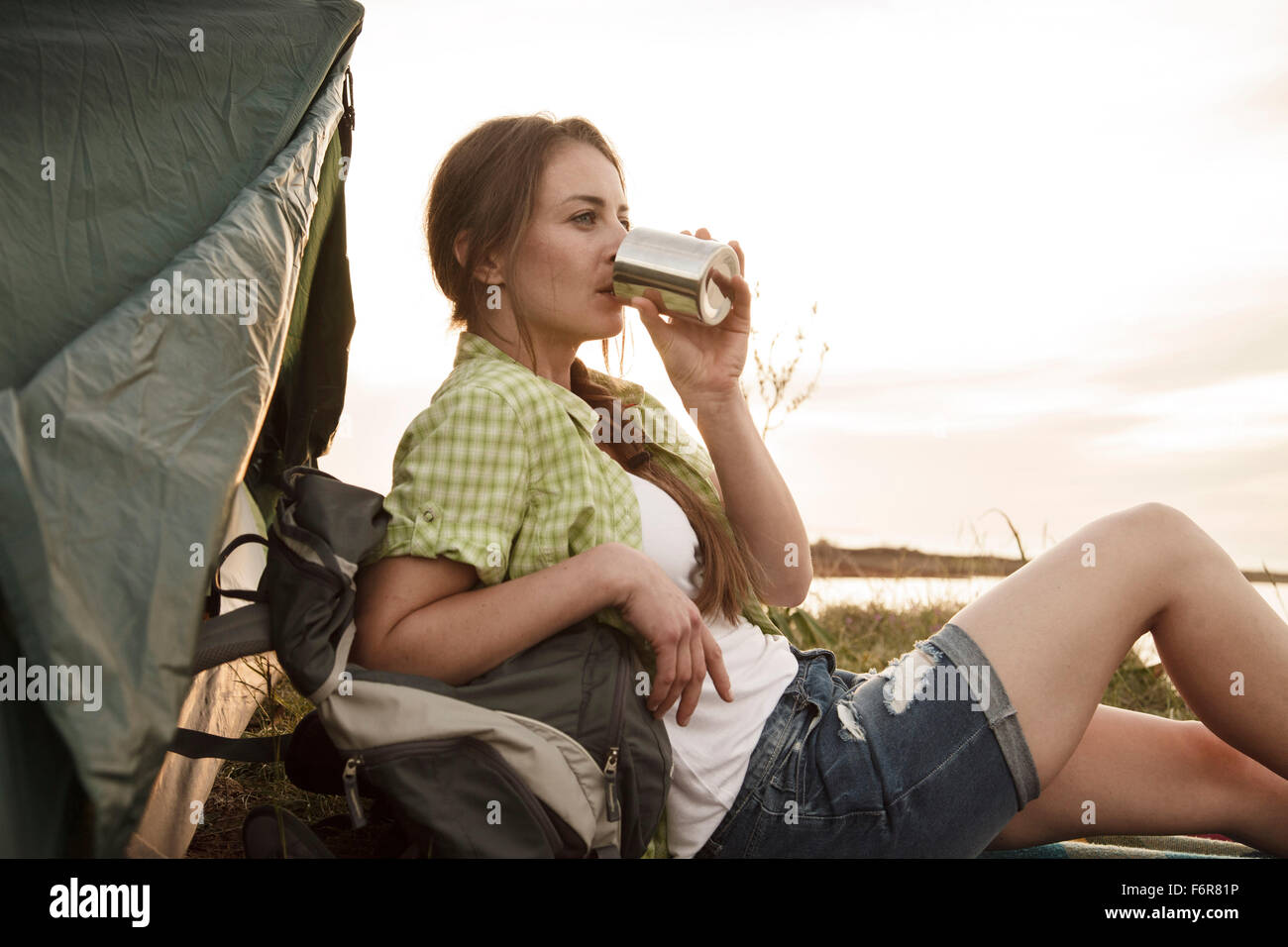 Young woman at campsite drinking cup of coffee Stock Photo