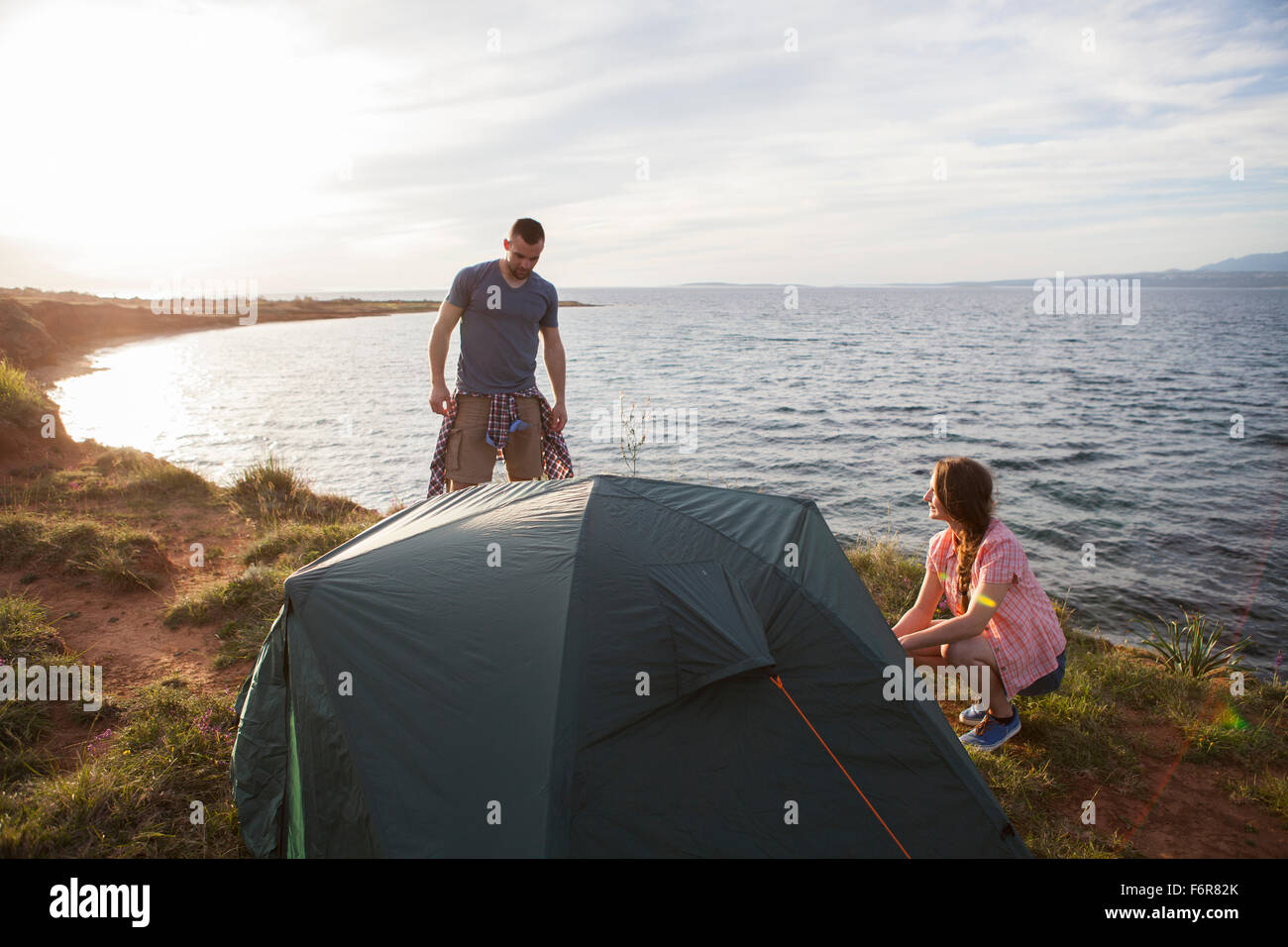 Young couple building up tent on water's edge - Stock Image