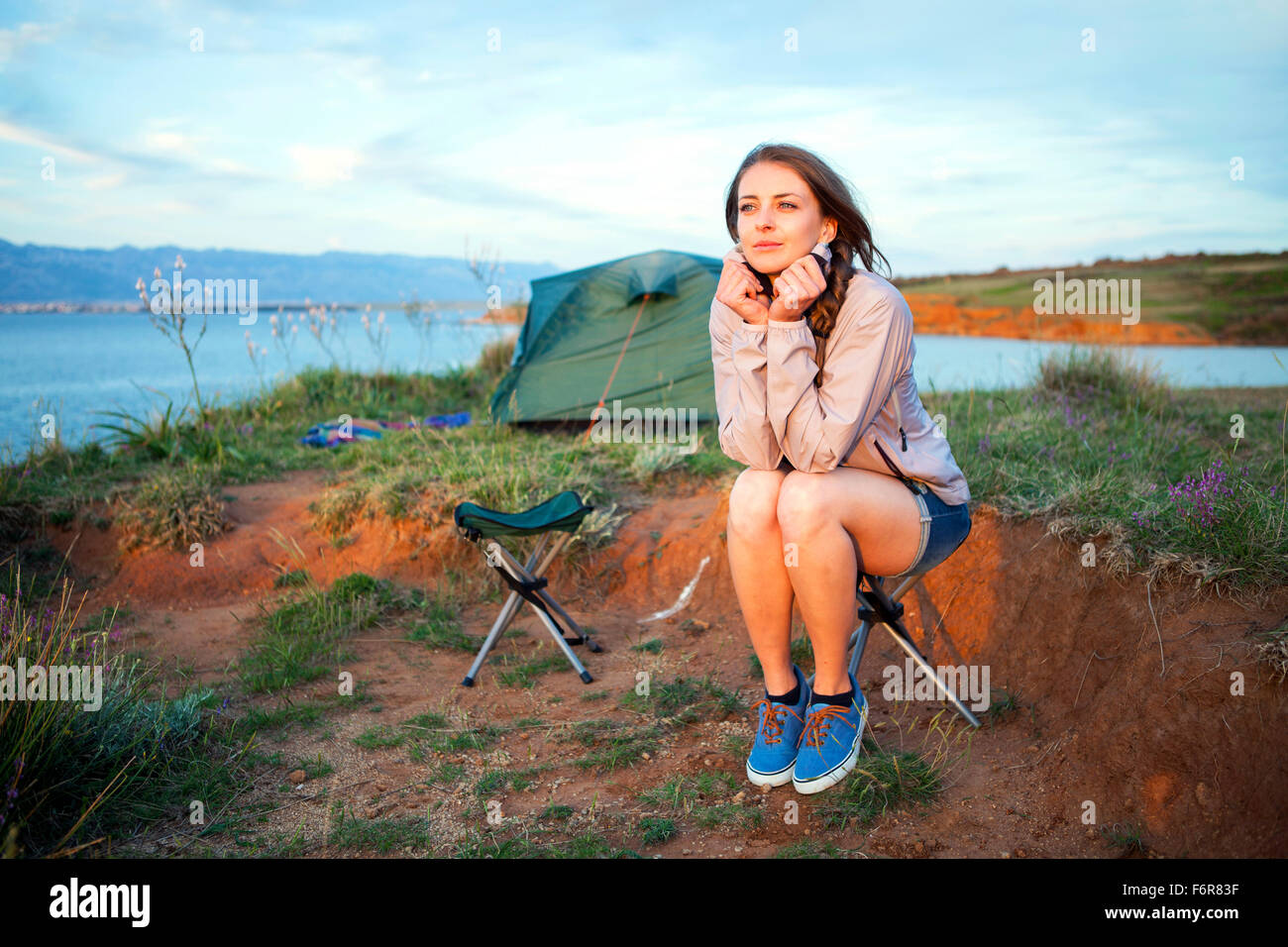Young woman at campsite day dreaming - Stock Image