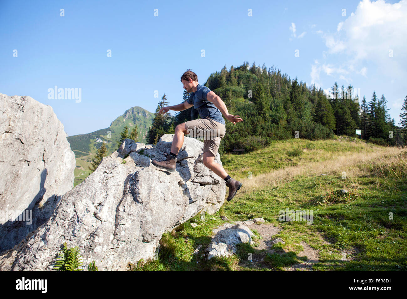Young man hiking in mountain landscape - Stock Image