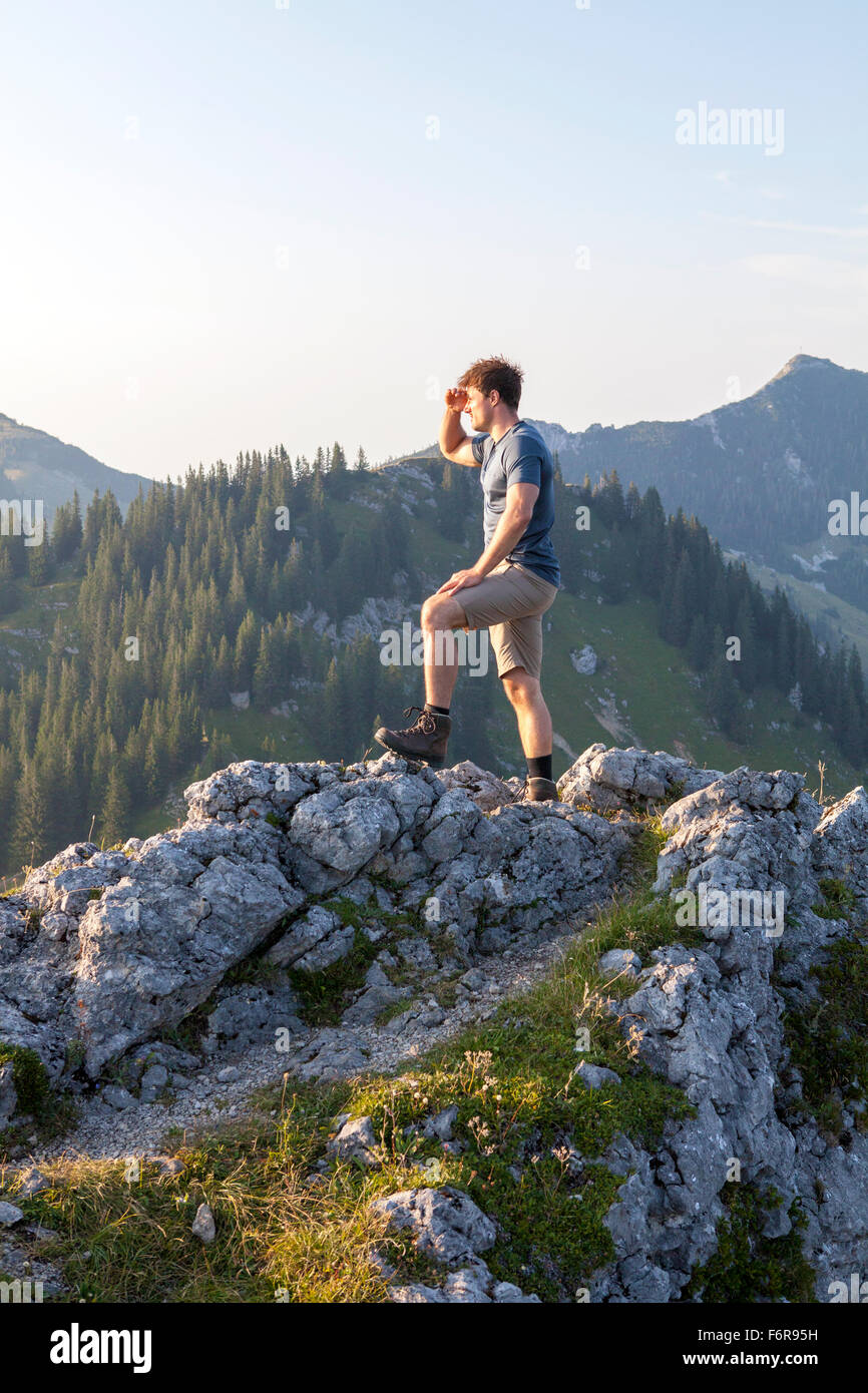 Young man overlooking mountain landscape - Stock Image