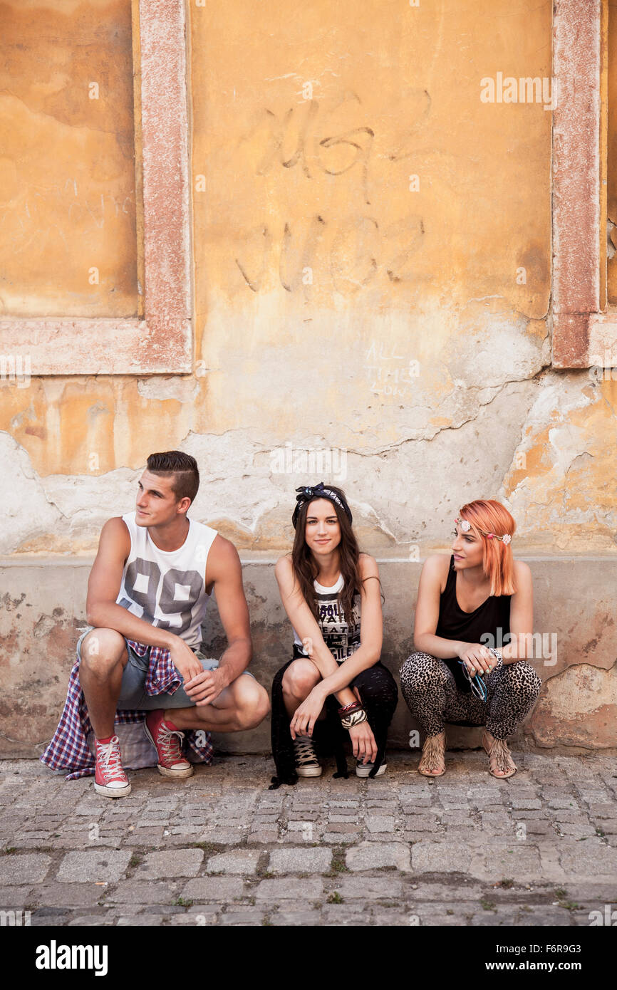 Young people in hippie style fashion crouching on sidewalk - Stock Image