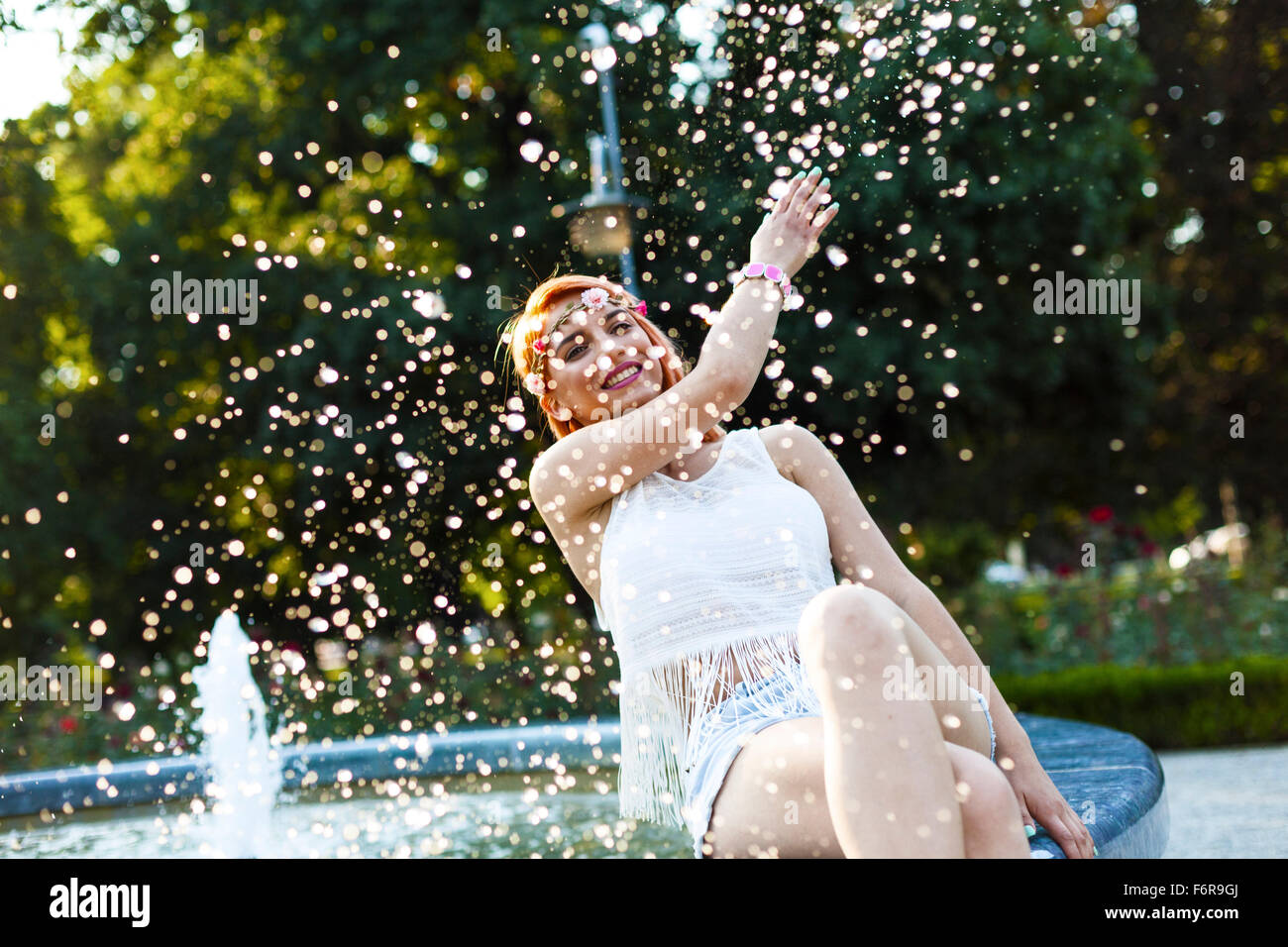 Young woman in hippie style fashion splashing water - Stock Image