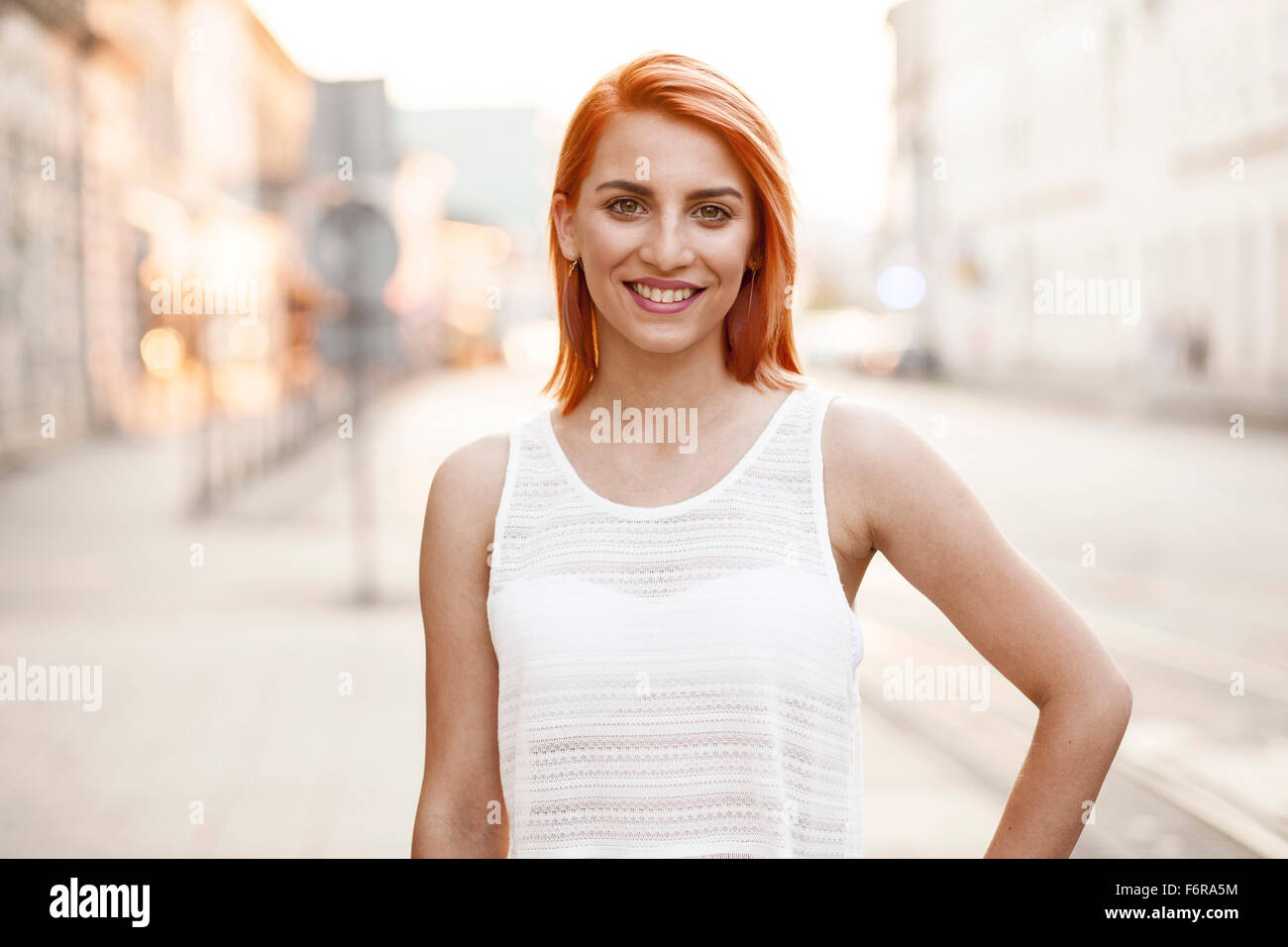 Redheaded woman in white summer dress - Stock Image