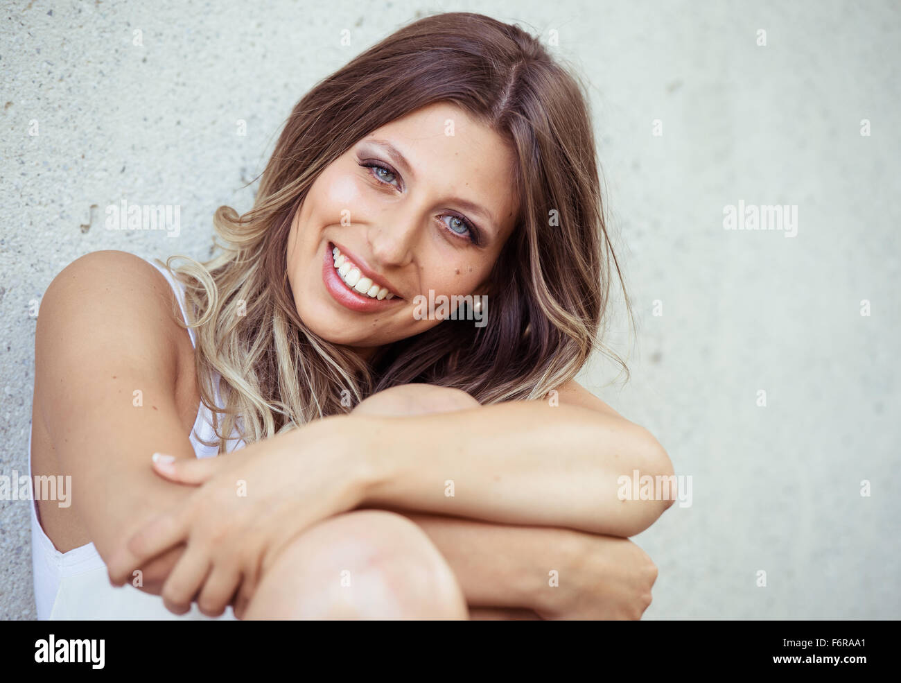 Young, handsome woman, smiling, with long hair and blue eyes, portrait - Stock Image