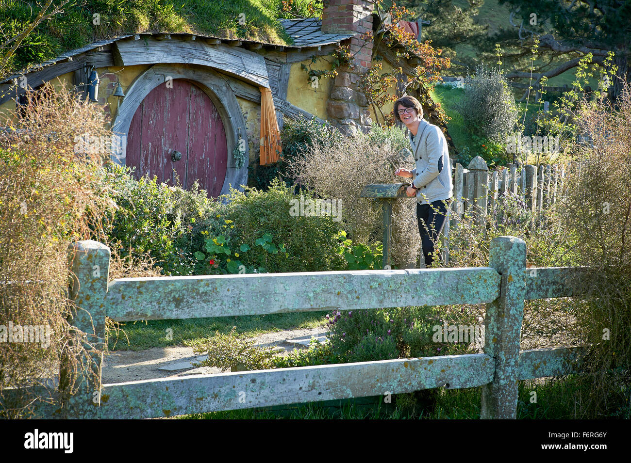 Teenager collecting mail from mailbox outside hobbit house. - Stock Image