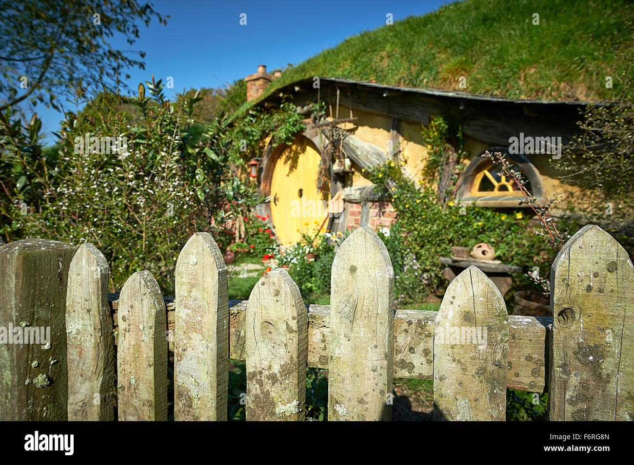 Fence detail with hobbit home in background. Hobbiton New Zealand - Stock Image