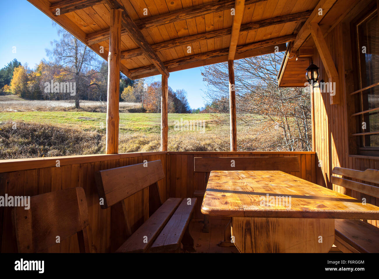 Wooden porch, veranda of a small mountain house. The sun is shining and the sky is clear blue. - Stock Image
