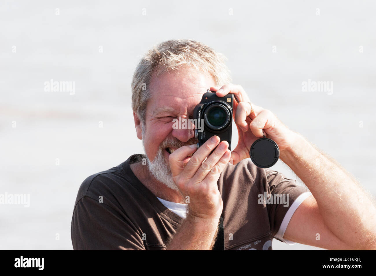 Man taking photo photograph with camera Lumix photographing one eye closed concentrating - Stock Image